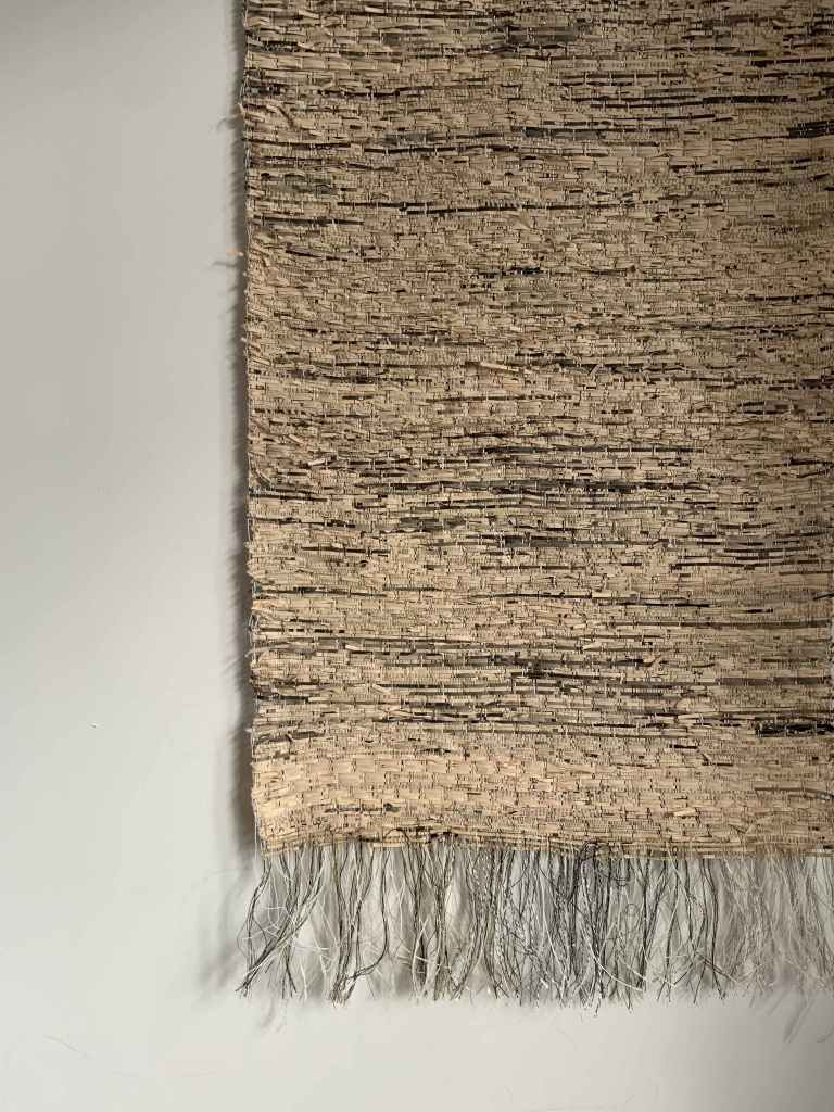 Handwoven paper wall art with floating threads